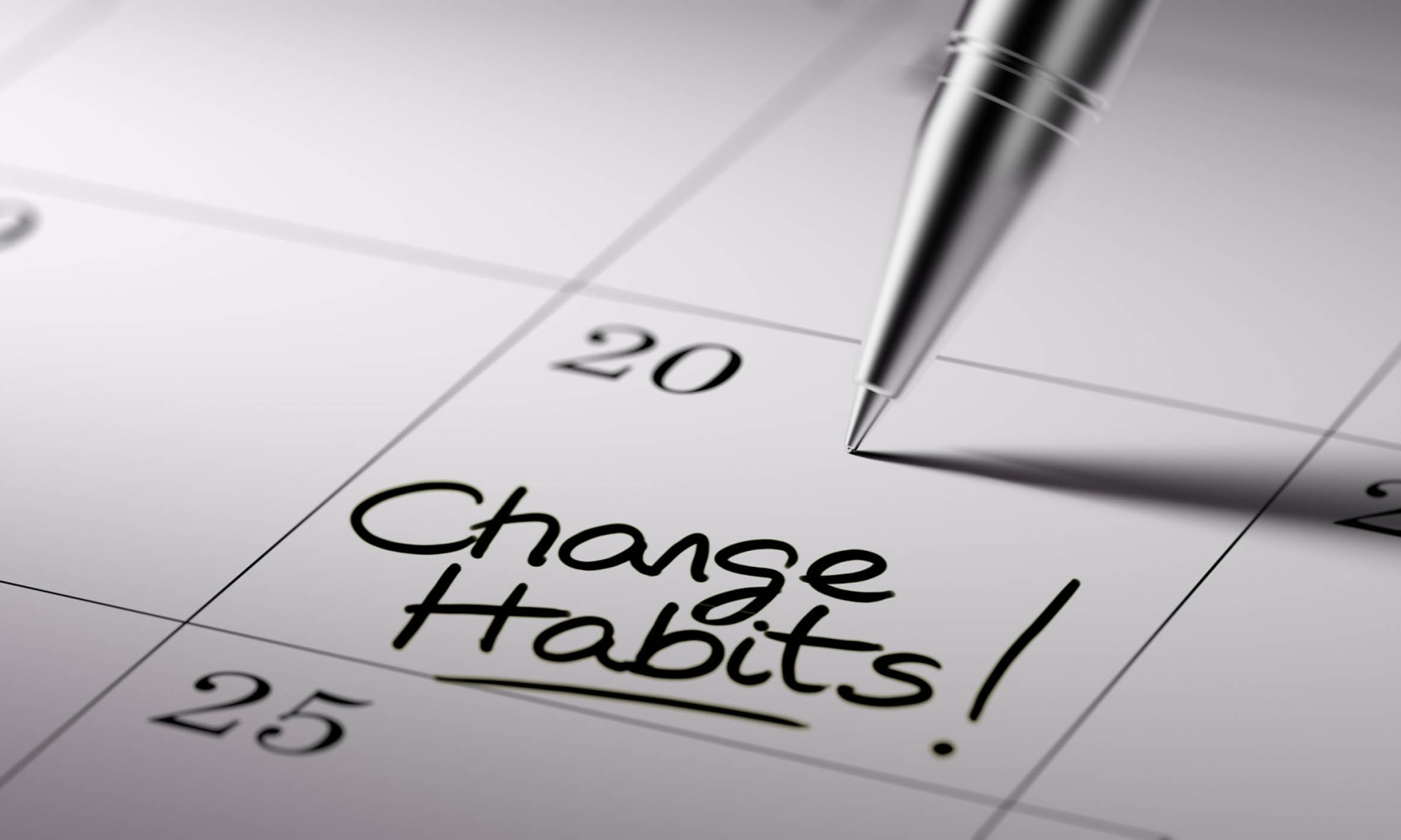 "Closeup of a calendar with a pen writing the words ""Change Habits!"" on a specific day."