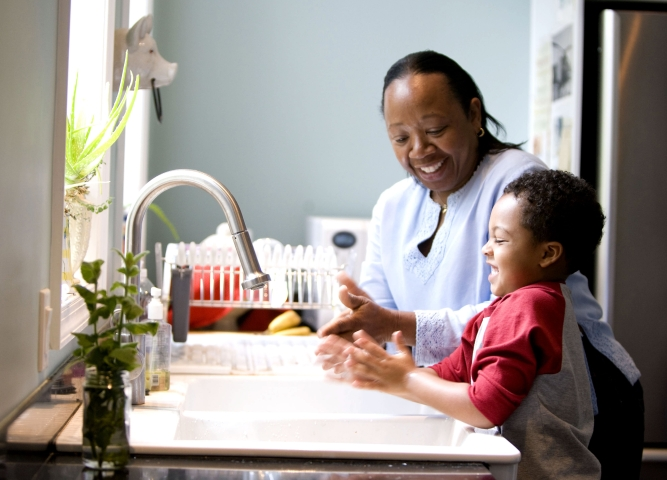 African American mother washing hands with her son